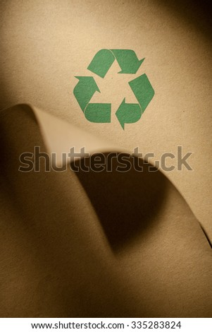 Recycling logo on recycled paper.  - stock photo