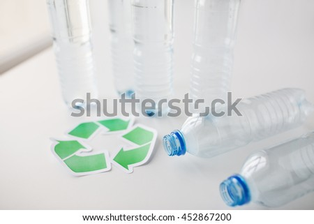 recycling, reuse, garbage disposal, environment and ecology concept - close up of empty plastic water bottles with green recycle symbol on table - stock photo