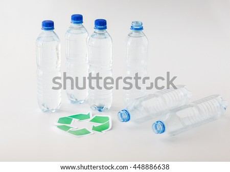 recycling, reuse, garbage disposal, environment and ecology concept - close up of plastic water bottles with green recycle symbol on table - stock photo