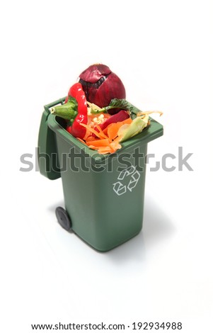 Recycling rubbish in a garbage bin with vegetable scraps / organic waste inside to turn into compost. - stock photo