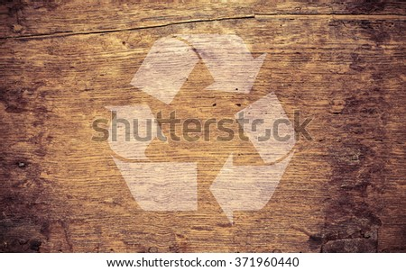 Recycling symbol on brown grungy wooden background texture. Concept of environment, reuse and green thinking. - stock photo