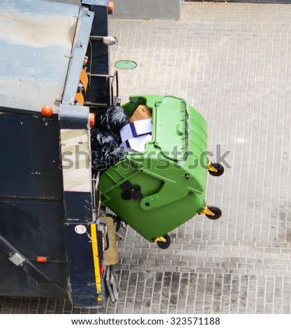 Recycling truck picking up bin - stock photo