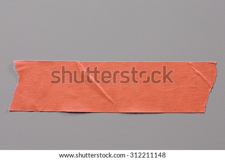 Red Adhesive Tape on Grey Background with Real Shadow. Top View of  Masking Tape, Label or Paper Tag. Sticker Close Up with Copy Space for Text or Image - stock photo