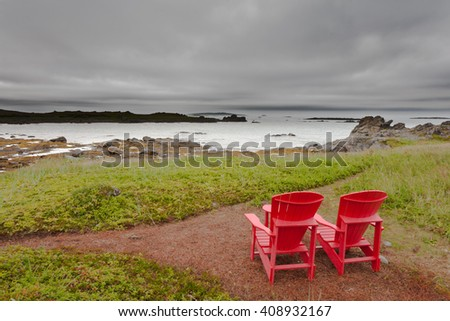 Red Adirondack Chairs overlooking coastal landscape of Newfoundland, NL, Canada