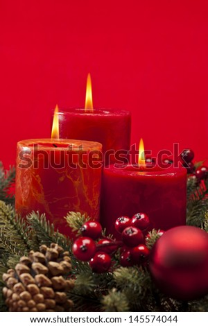 Red advent flower arrangement with burning candles