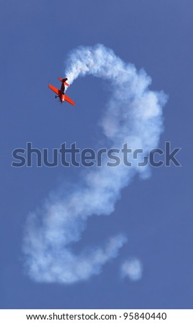 Red aerobatic airplane in the sky with question mark - stock photo