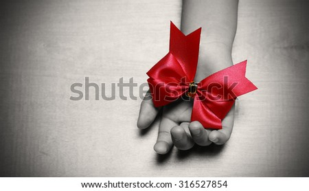 red aids ribbon in hand - stock photo