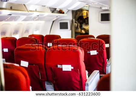 Red airplane seats at the front of a plane