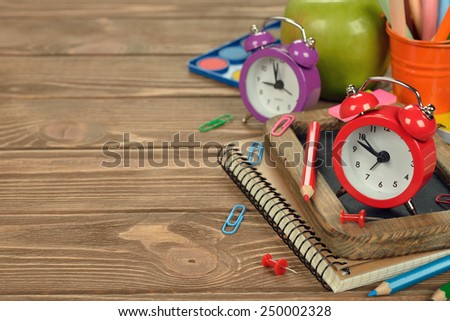 Red alarm clock and office supplies on a brown background