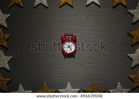 Red alarm clock on slate background with frame of golden and silver stars, Christmas decoration.