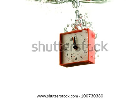 Red alarm clock thrown into the water on white - stock photo