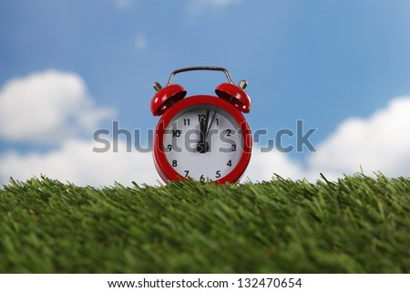 Red alarm clock with two bells on green field - stock photo
