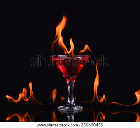 Red alcohol cocktail in glass with fire - stock photo
