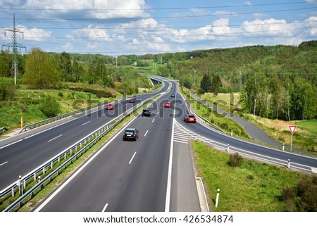 Red and black cars on an asphalt highway between lush forests in the countryside. In the distance the bridge and Electronic toll gate. Sunny spring day with dramatic white clouds. View from above. - stock photo