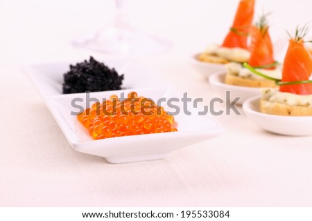 Red and black caviar with smoked salmon rolls, top view
