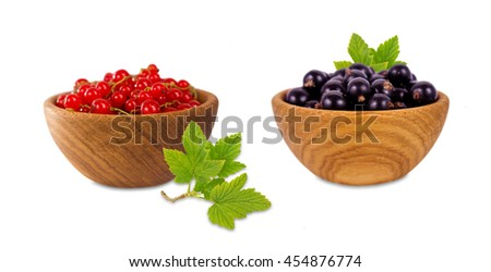 Red and black currant in a wooden bowl. Ripe and tasty currant isolated on white background. Red berries with leaves. - stock photo