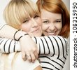 red and blond haired girls friends laughing and hug - stock photo