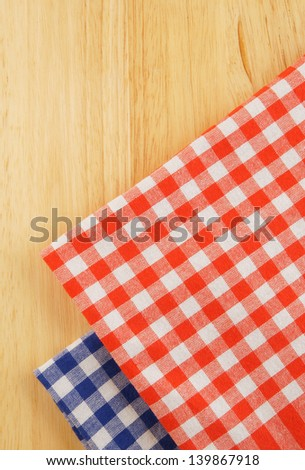Red and blue checked tablecloth on wooden background - stock photo