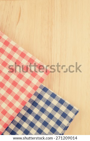 Red and blue checked tablecloth on wooden background