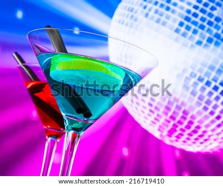 red and blue cocktail with sparkling disco ball background with space for text, dance disco concept - stock photo