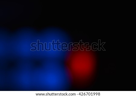 Red and blue defocused blurry circular lights glowing soft in the darkness. They soothe, brings a positive and located at the bottom left of the photo. - stock photo