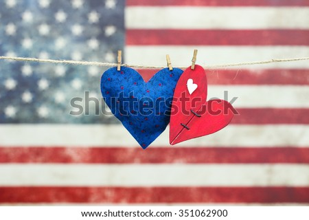 Red and blue hearts hanging on rope clothesline in front of antique rustic American canvas flag blurred in background - stock photo