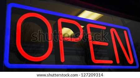 Red and blue neon open sign at store with background interior lights - stock photo
