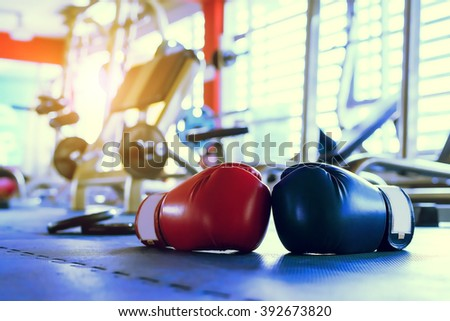 Red And Blue oxing gloves hanging on a Blue wall IN Gym Fitness  - stock photo