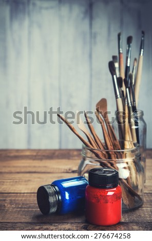 Red and blue paint and artist's tools on rustic background. Selective focus. - stock photo