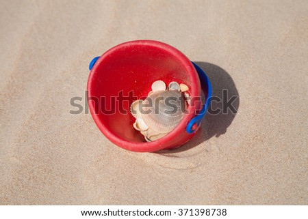 red and blue plastic baby infant toy bucket full of sea shells on golden sand beach - stock photo