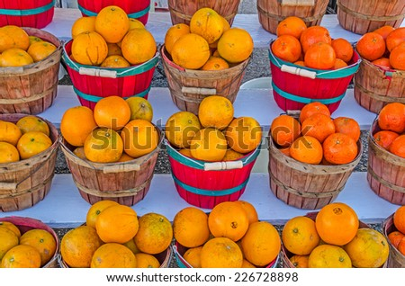 Red and brown baskets overflowing with Honeybell Oranges from Florida nicely displayed along a street - stock photo
