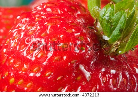 Red and fresh morning dew covered strawberries on a breakfast table