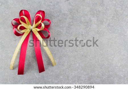 Red and gold bow of ribbon on cement background for fill text in space - stock photo