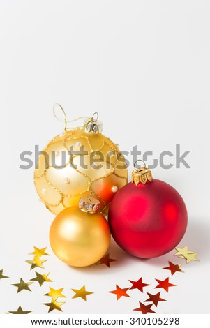 Red and gold Christmas baubles and stars on white background
