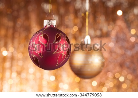 Red and gold christmas baubles on background of defocused golden lights. - stock photo