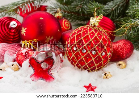 red  and gold christmas decorations in snowfall under fir tree - stock photo