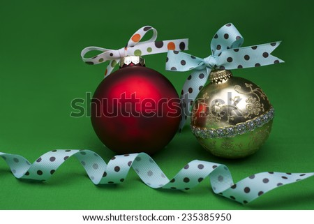 Red and Gold Christmas Ornaments with Poka Dots Bow Tie on Green Background