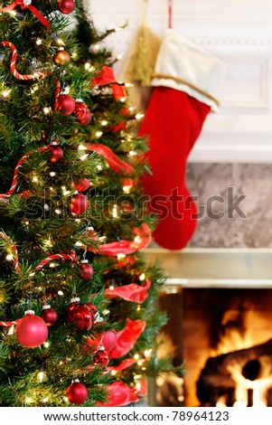 Red and gold decorated Christmas tree by the fire - stock photo
