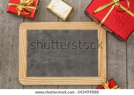 Red and gold gift boxes with over wooden background with blackboard - stock photo