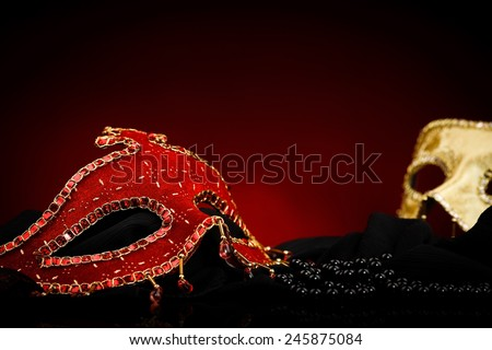 Red and golden carnival masks and black pearl, red and black background - stock photo