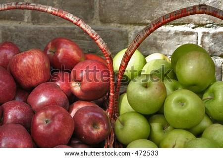 Red and green apples in baskets - stock photo
