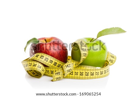 red and green apples with measuring tape on a white background - stock photo