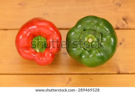 Red and green capsicum peppers on a wooden kitchen table - stock photo