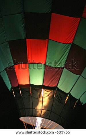Red And Green Checkered Hot Air Balloon With Burners on at Night - stock photo
