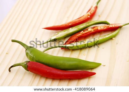 Red and green chilli peppers on chopping board - stock photo