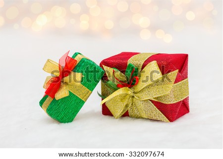 Red and green Christmas gift box with shiny golden ribbon. Bokeh with glow effect on white background - stock photo