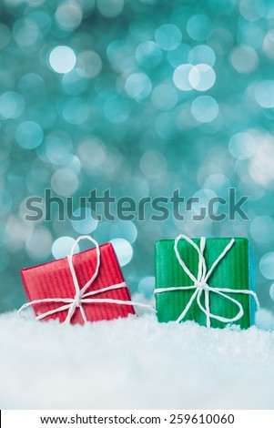 Red and green gift boxes in snow on abstract background - stock photo