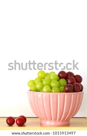 Red and green grapes in pretty pink bowl in vertical format with room for text
