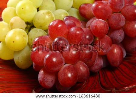 Red and green grapes/Ready to eat/Fat juicy red and green grapes on wooden carved tray - stock photo