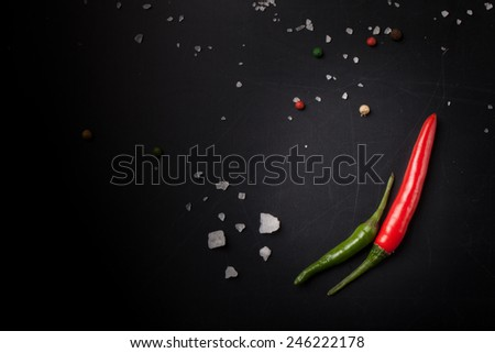 Red and green hot chilli pepper with sea salt and colored pepper on black background. Toned. - stock photo